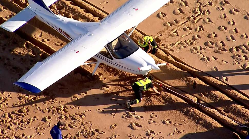 Crews attempt to tow the Tecnam P2008 from the Collaroy sands.(ABC News)