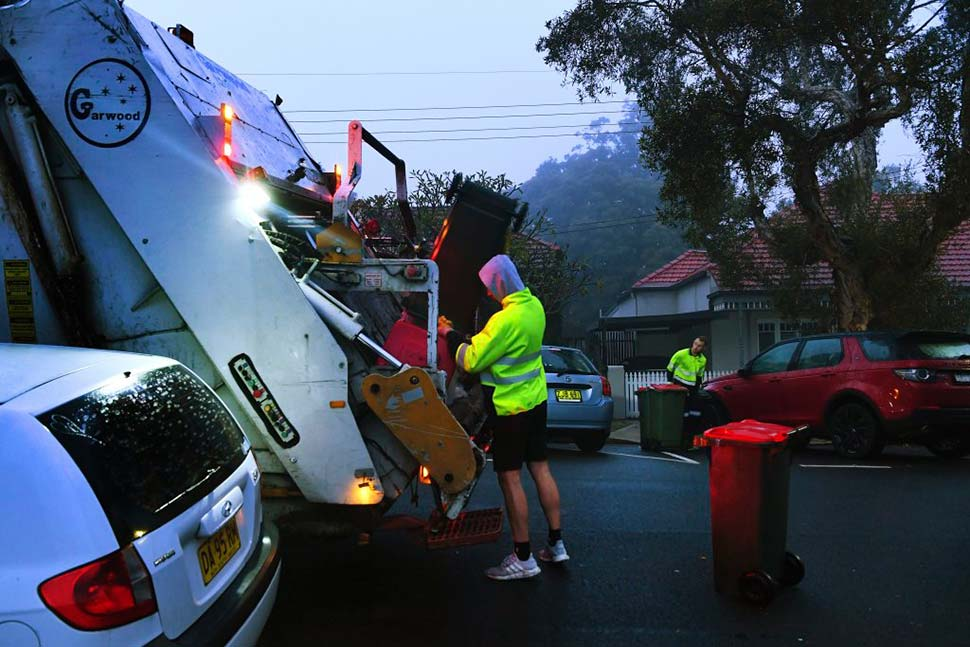 Men-load-rubbish-into-a-truck-that-collects-residential-waste-along-Macauley-street-in-Leichhardt.CREDITKATE-GERAGHTY